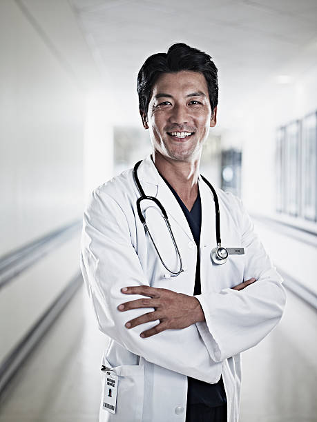 Portrait of smiling doctor standing with arms crossed in hospital corridor stock photo