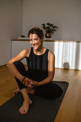 Portrait of Smiling Early 30s Woman Sitting in Yoga Studio