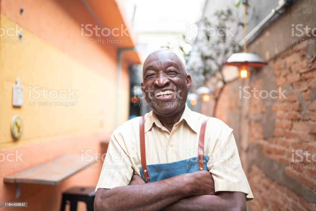 Portrait of smiling elderly waiter looking at camera Portrait of smiling elderly waiter looking at camera 70-79 Years Stock Photo