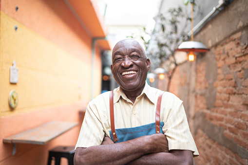 Portrait Of Smiling Elderly Waiter Looking At Camera Stock Photo - Download Image Now