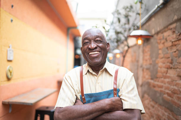 Portrait of smiling elderly waiter looking at camera stock photo