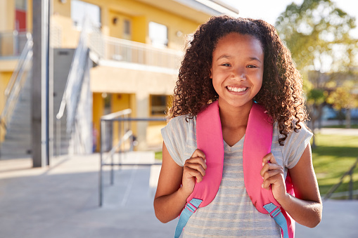 istock Portrait of smiling elementary school girl with her backpack 1045331466