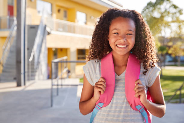 Portrait of smiling elementary school girl with her backpack Portrait of smiling elementary school girl with her backpack 12 13 years stock pictures, royalty-free photos & images