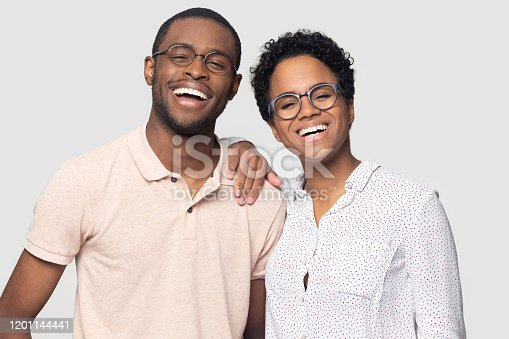 Headshot portrait of overjoyed african American couple in glasses isolated on grey studio background laugh look at camera, happy ethnic black man and woman smiling posing for picture together
