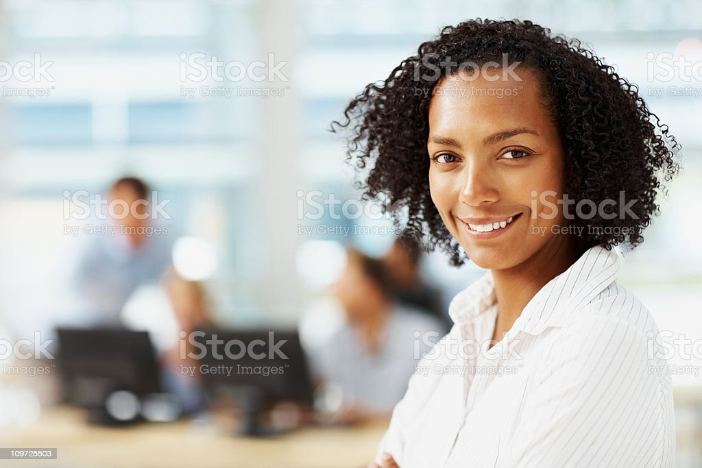 Portrait of smiling executive with colleagues in the background stock photo