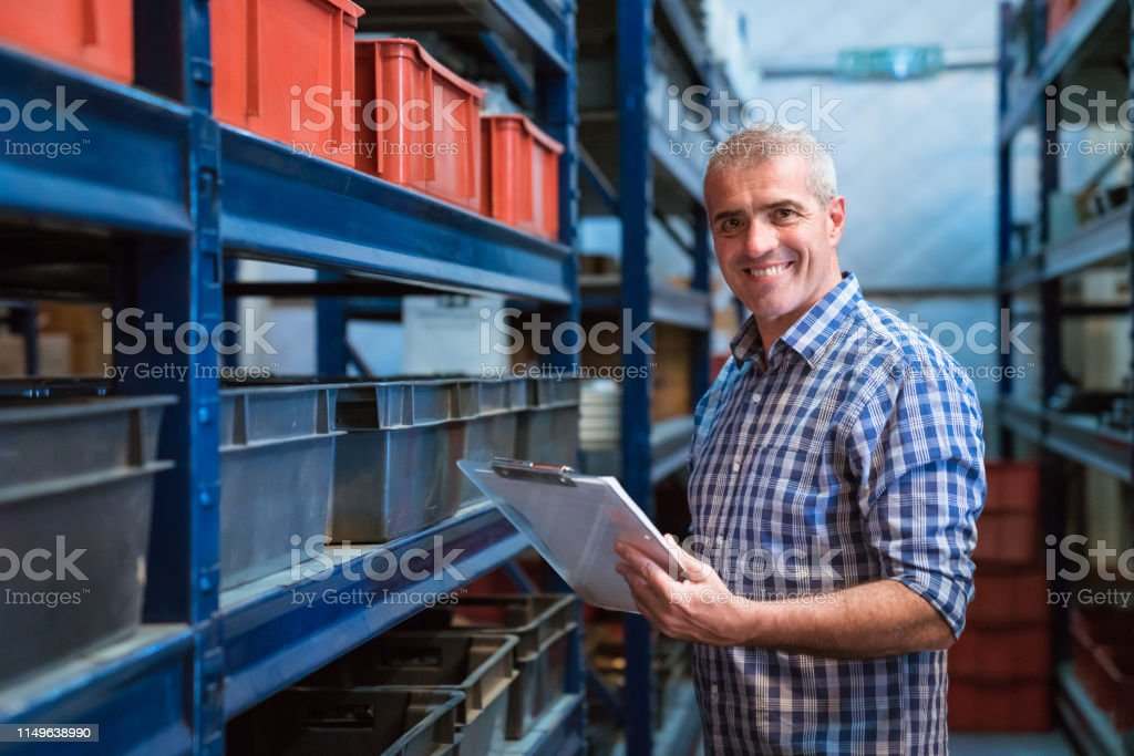 Portrait of smiling factory manager with clipboard Portrait of smiling factory manager holding clipboard. Mature male worker is working in warehouse. He is wearing checked patterned shirt. 55-59 Years Stock Photo