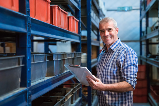 Portrait Of Smiling Factory Manager With Clipboard Stock Photo - Download Image Now