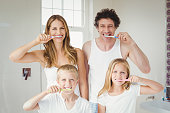 Portrait of smiling happy family brushing teeth at home