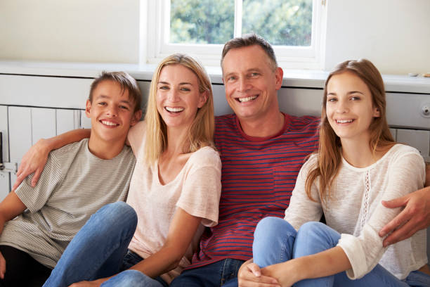Portrait Of Smiling Family Relaxing On Seat At Home Portrait Of Smiling Family Relaxing On Seat At Home four people stock pictures, royalty-free photos & images