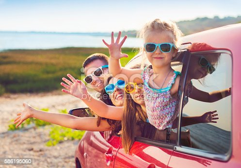 istock Portrait of smiling family with children at beach in car 586195060
