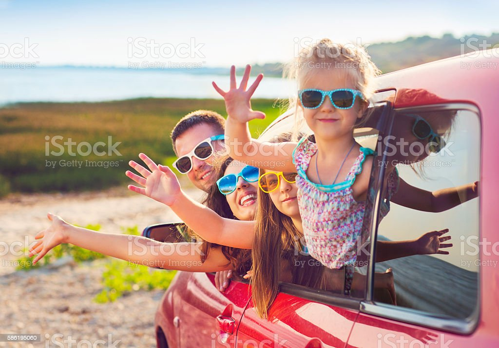Portrait of smiling family with children at beach in car stock photo