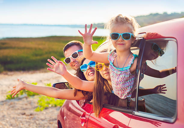 portrait of smiling family with children at beach in car - family vacation stock photos and pictures