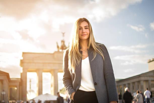 porträt von lächelnden modische junge frau vor dem brandenburger tor in berlin, deutschland. - deutsche frauen stock-fotos und bilder