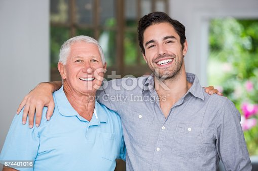 istock Portrait of smiling father and son with arm around 674401016
