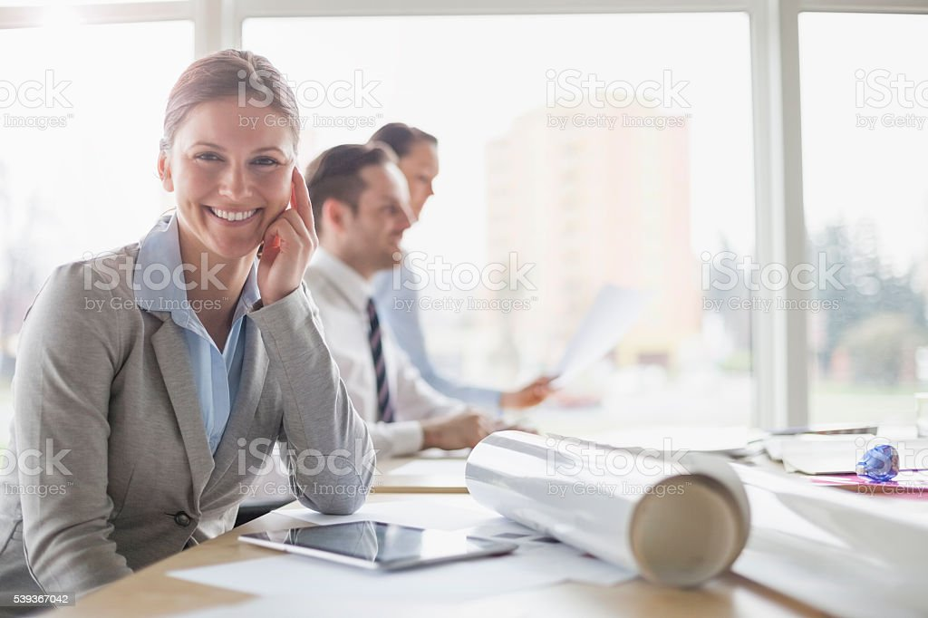 Portrait of smiling female architect sitting at desk with stock photo
