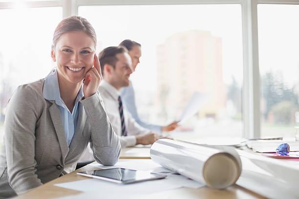 Porträt von lächelnder Architektin beim Sitzen am Schreibtisch mit – Foto
