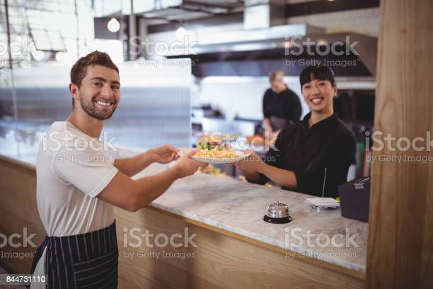 Portrait of smiling female chef and waiter holding plate at counter picture id844731110?b=1&k=6&m=844731110&s=612x612&h=moedjynqjgpdn7rdctyo7pvtzuii4h6vrswzdqypnim=