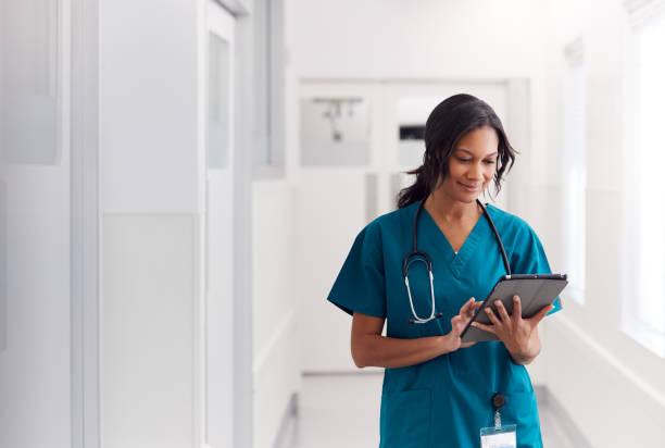 Portrait Of Smiling Female Doctor Wearing Scrubs In Hospital Corridor Holding Digital Tablet stock photo