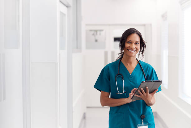 Portrait Of Smiling Female Doctor Wearing Scrubs In Hospital Corridor Holding Digital Tablet stock photo