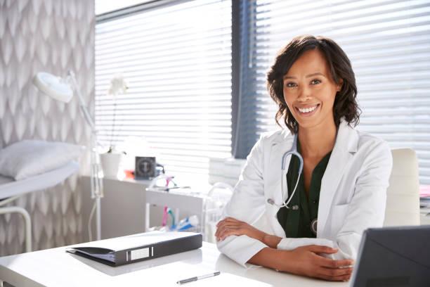 笑顔の女性ドクターのポートレート事務所で机の後ろに座る聴診器付き白衣を着て - 医院 ストックフォトと画像