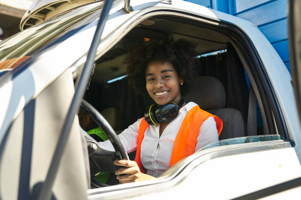 Portrait of smiling female engineer driving truck stock photo