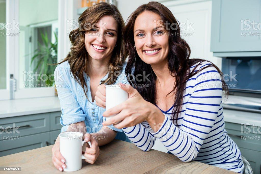 Retrato de sonriente amigas con tazas de café mientras estaba sentado en la mesa - foto de stock