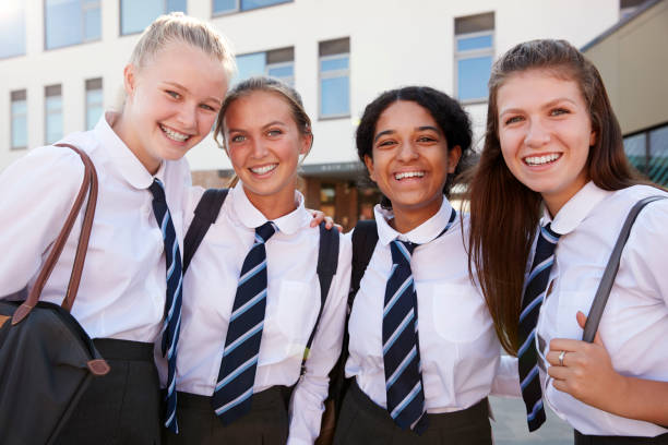portrait of smiling female high school students wearing uniform outside college building - униформа стоковые фото и изображения