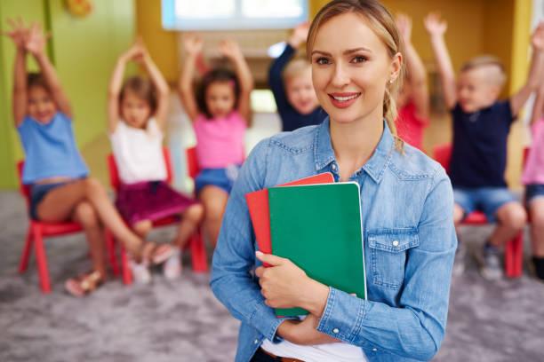Portrait of smiling female teacher in the preschool stock photo