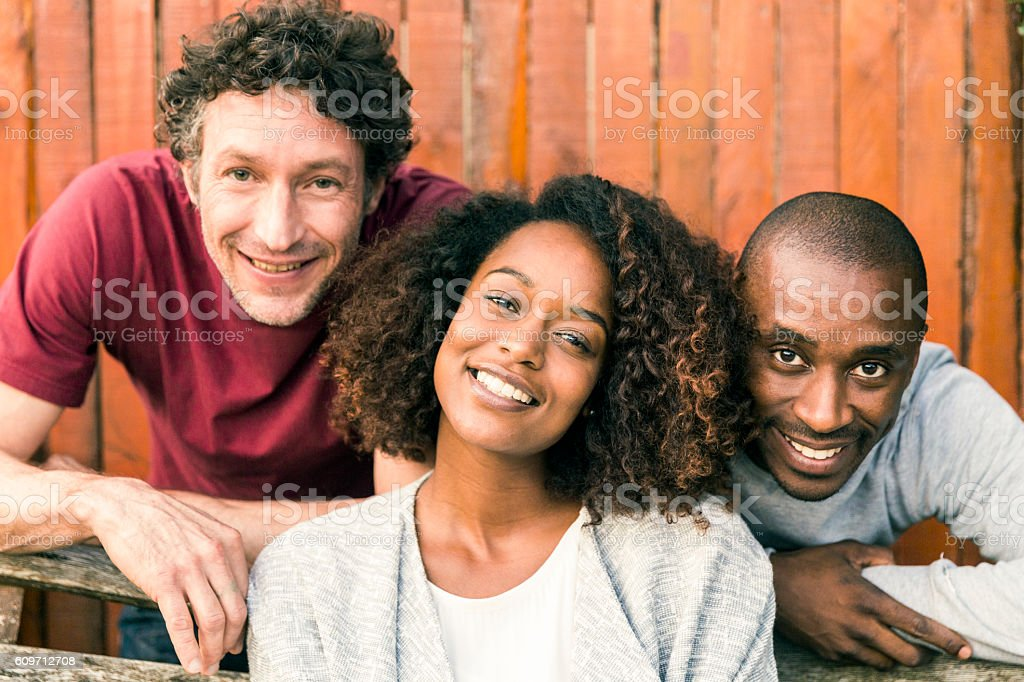 Portrait of smiling friends against wooden fence - foto de acervo