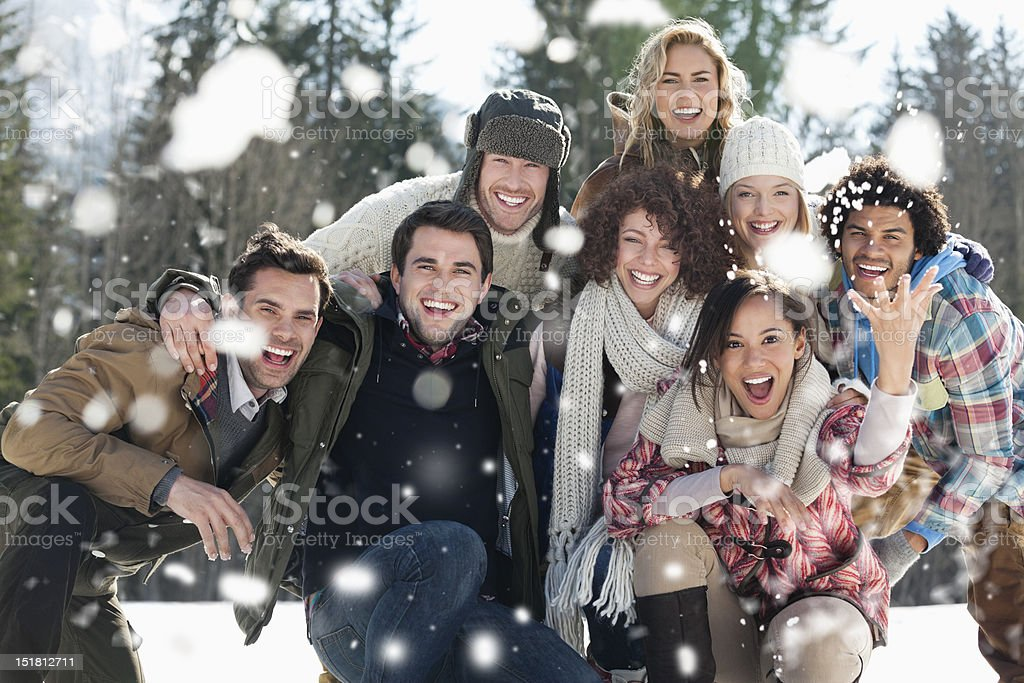 Portrait of smiling friends throwing snow stock photo