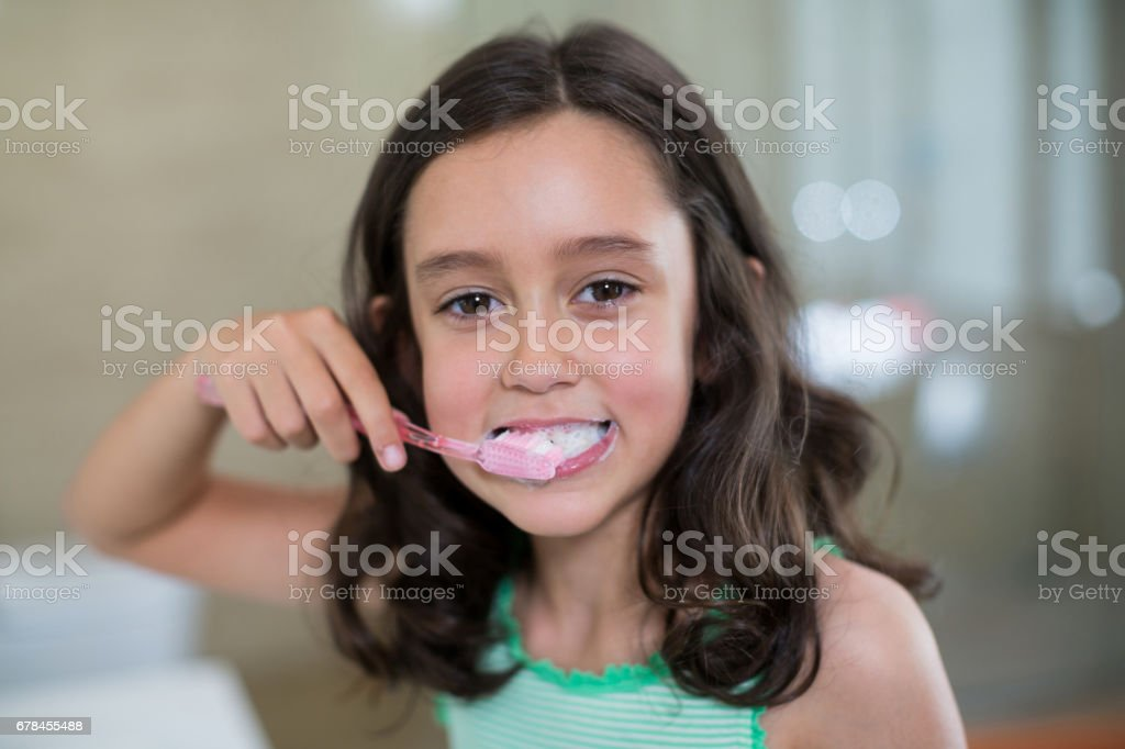 Portrait of smiling girl brushing her teeth in bathroom royalty-free stock photo