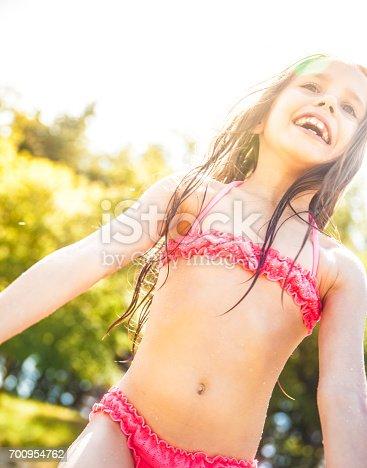 istock Portrait Of Smiling Girl Enjoying Her Beach Holiday 700954762