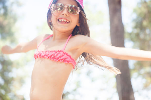 portrait of smiling girl enjoying her beach holiday - girl alone in swimsuit stock photos and pictures