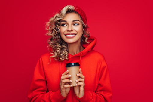 Portrait of smiling girl holding disposable mug of coffee