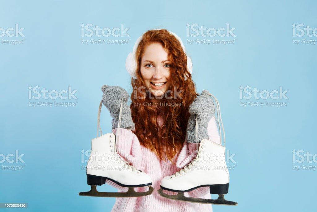 Portrait of smiling girl holding ice skates