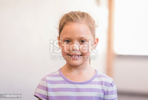 Portrait of smiling girl. Cute female kid is wearing casuals. She is at school.