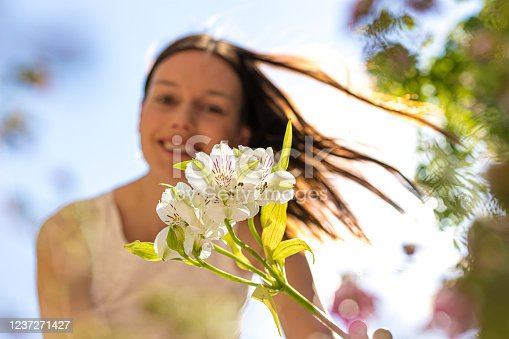 Portrait of smiling girl looking at a white flower with wind in her hair. Background is defocused. Royalty free stock photo.