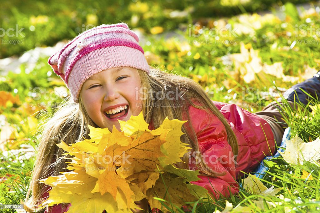 Portrait of smiling girl with dry maple leaves royalty-free stock photo