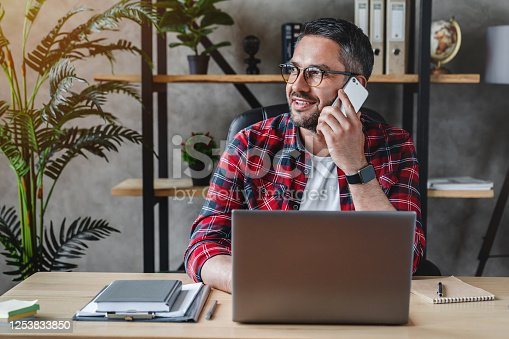 Portrait of smiling grey hair man with beard sitting front table with laptop, talking on phone