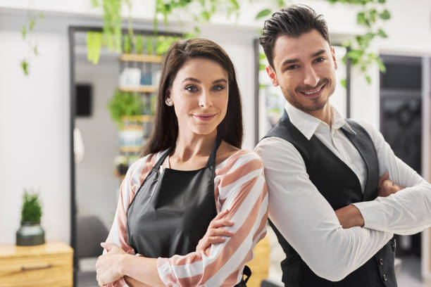 Portrait of smiling hairstylist and his assistant stock photo