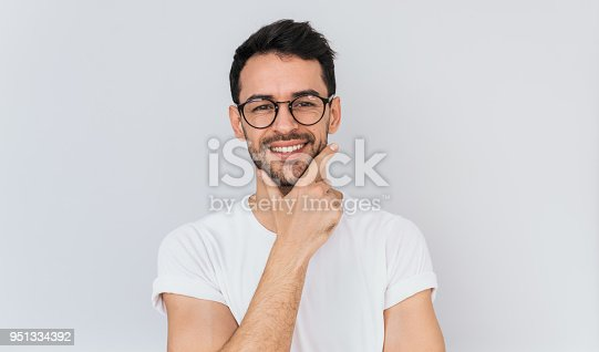 951331990 istock photo Portrait of smiling handsome male worker keeps hand under chin, wears casual white T-shirt and optical round glasses, looks directly into camera with happy confident expression.People, emotion conept 951334392