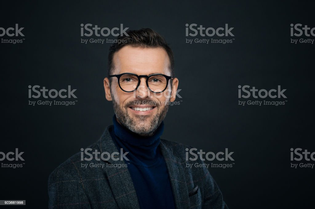 Portrait of smiling handsome man, dark background Portrait of handsome businessman in tweed jacket and glasses against black background, smiling at camera. 30-39 Years Stock Photo
