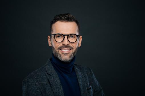 Portrait Of Smiling Handsome Man Dark Background Stock Photo - Download Image Now