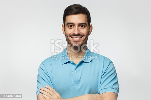 1045886560 istock photo Portrait of smiling handsome man in blue polo shirt, standing with crossed arms isolated on grey background 1090878400