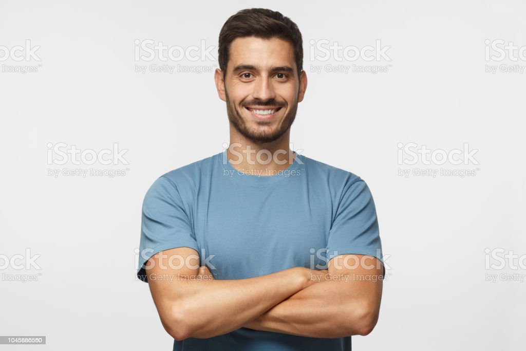 Portrait of smiling handsome man in blue t-shirt standing with crossed arms isolated on grey background royalty-free stock photo