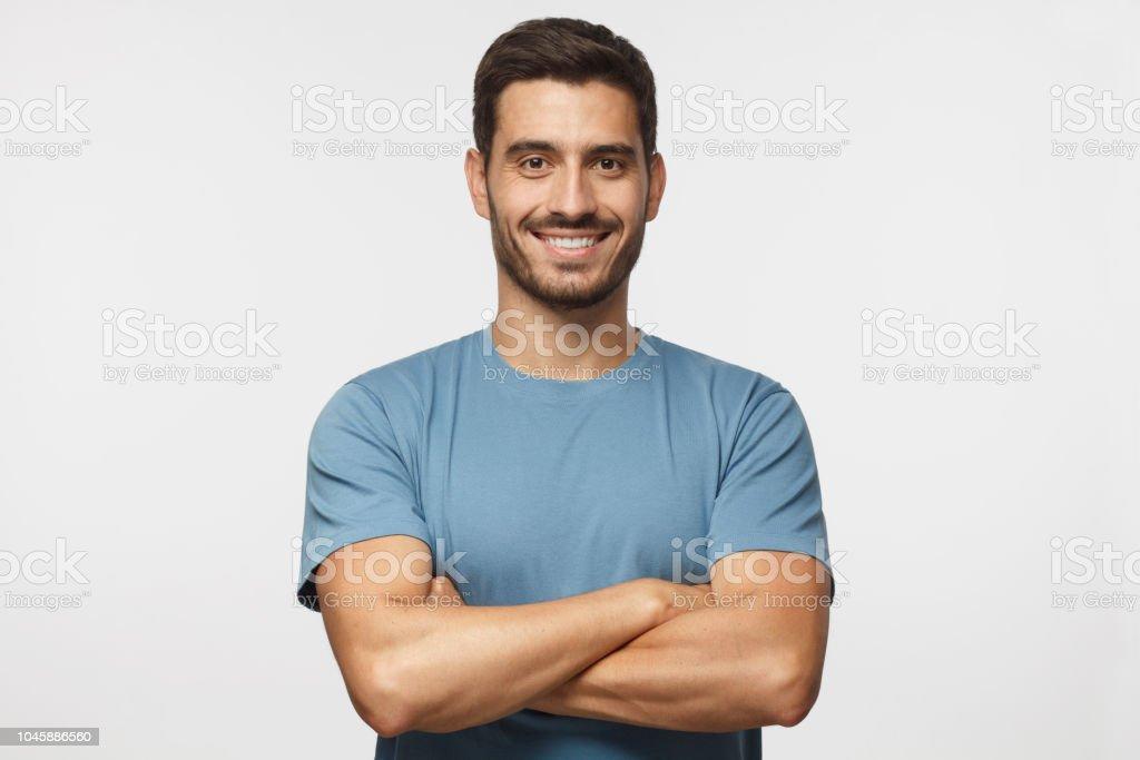 교차 팔 회색 배경에 고립 된 블루 티셔츠 서에서 잘생긴 남자를 미소의 초상화 royalty-free 스톡 사진