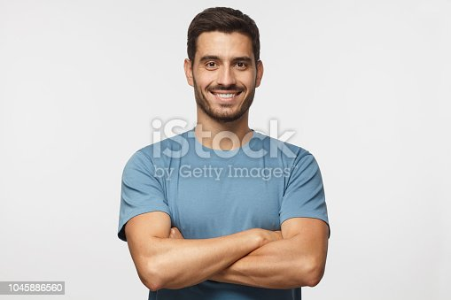 istock Portrait of smiling handsome man in blue t-shirt standing with crossed arms isolated on grey background 1045886560