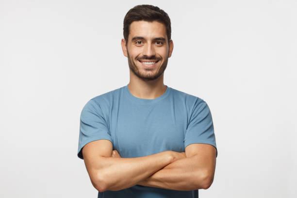 portrait de sourire bel homme dans la position de t-shirt bleu avec bras croisés isolés sur fond gris - homme photos et images de collection