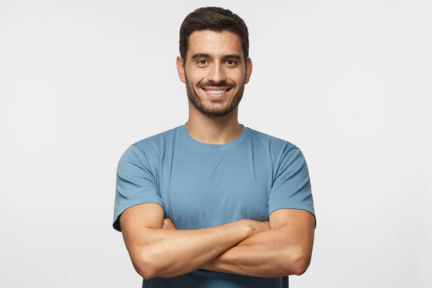 Portrait of smiling handsome man in blue t-shirt standing with crossed arms isolated on grey background stock photo