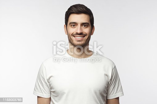 1093999692 istock photo Portrait of smiling handsome man in white t-shirt looking at camera, isolated on gray background 1153003765